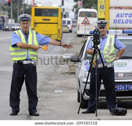 ZRENJANIN, SERBIA - CIRCA AUGUST 2014: Police officer controls driving speed at local road, circa August 2014 in Zrenjanin