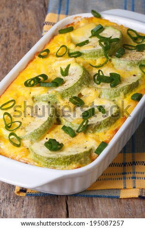 Zucchini baked with cheese, eggs and onion closeup in a white dish. vertical