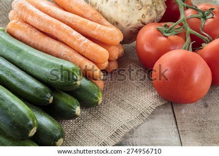Zucchini, carrots, celery root and tomatoes on wooden table. Copy space. - stock photo