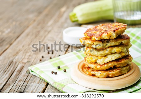 zucchini corn fritters on a dark wood background. the toning. selective focus - stock photo