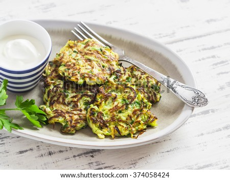 Zucchini fritters with herbs on a ceramic plate on a light wooden background. Healthy, vegetarian food - stock photo