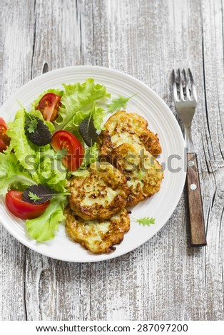zucchini pancakes and fresh vegetable salad on white plate on a light wooden background - stock photo