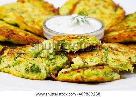 Zucchini Pancakes With  Sour Cream in White Plate.