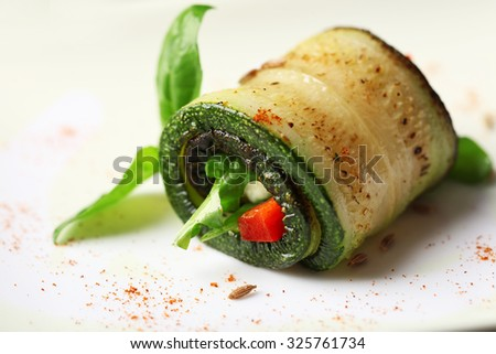 Zucchini roll with cheese, bell peppers and arugula on plate, close-up - stock photo