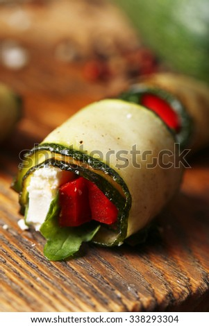 Zucchini rolls with cheese, bell peppers and arugula, close-up - stock photo