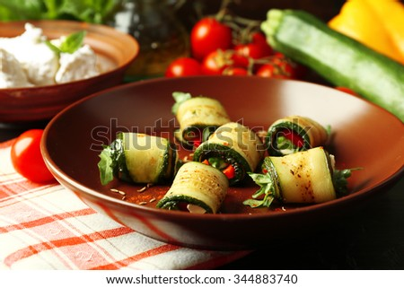 Zucchini rolls with cheese, bell peppers and arugula on plate, close-up - stock photo