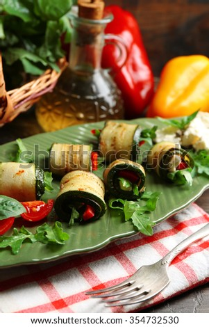 Zucchini rolls with cheese, bell peppers and arugula on plate, close-up, on table background - stock photo