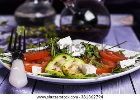 Zucchini salad with tomatoes, arugula and cheese - stock photo