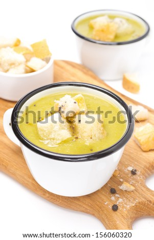 zucchini soup with croutons on a wooden board, close-up, isolated - stock photo