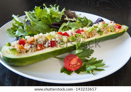 Zucchini stuffed with quinoa and vegetables on a white plate