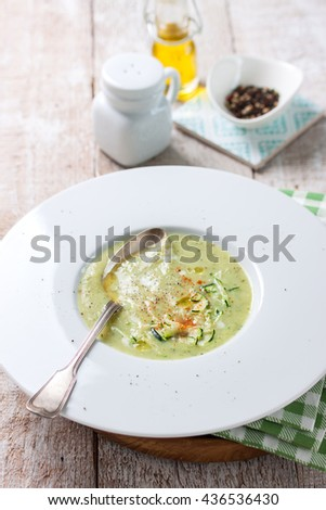 Zucchini vegetable creamy soup puree in a bowl on a wooden background, top view