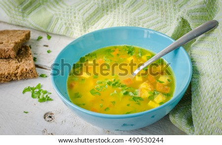 Zuppa Imperiale - Italian soup with eggs and Parmesan cheese, dish of Emilia Romagna. Imperial soup on wooden table. Omelet in chicken broth with parsley in a bowl. Italian cuisine concept.