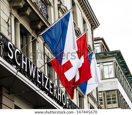 ZURICH-APRIL 21: Swiss and Zurich flags in front of Hotel Schweizerhof in Zurich, Switzerland on April 21, 2012. Zurich is home to a large number of financial institutions and banking giants. - stock photo