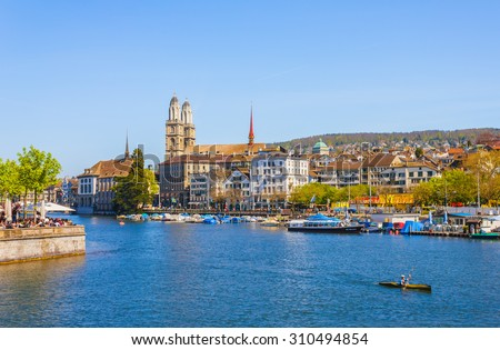 ZURICH, SWITZERLAND- APRIL 20: Cityscape of buildings and famous church of Zurich, capital of  Switzerland by the river on a sunny day on April 20, 2015.
