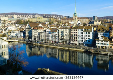 ZURICH, SWITZERLAND - DECEMBER 27, 2015: View of the east bank of the Limmat River, with the Predigerkirche church, locals and visitors. In Zurich, Switzerland