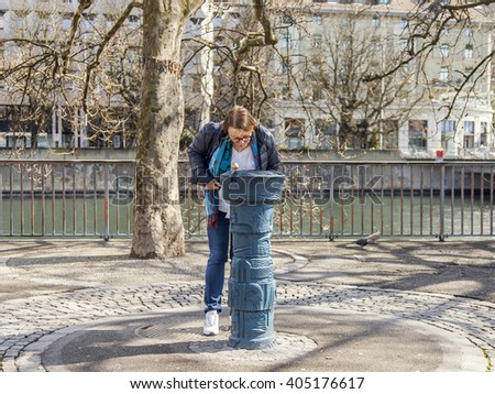 ZURICH, SWITZERLAND, on MARCH 26, 2016. Spring morning. The woman drinks water on the street