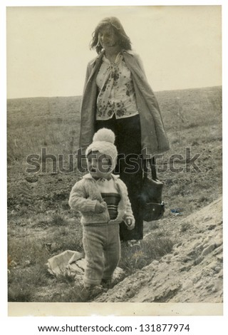 ZVOLEN, CZECHOSLOVAK REPUBLIC, CIRCA 1975 - Young mother and her child standing in a field - circa 1975 - stock photo