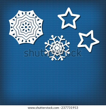 Paper snowflakes  on blue knitted background.