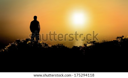 A black silhouette of a man standing on a beach and observing the sea sunrise or sunset - vector illustration - stock vector