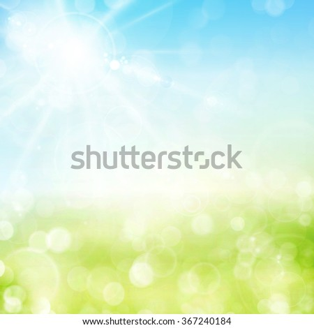 Abstract green spring background with blue sky and sun with lens flare. Blurry light dots and light effects give it a soft feeling for the spring, easter season.