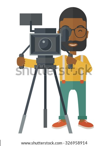 An african-american cameraman with beard and glasses looking through movie camera on a tripod vector flat design illustration isolated on white background. Vertical layout. - stock vector