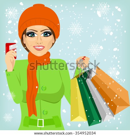 attractive woman shopping on christmas winter day holding credit card and bags