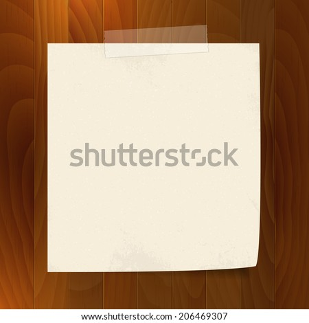 blank note paper with tape  on wood background. isolated.