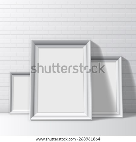 Blank white pictures frames on brick wall and floor