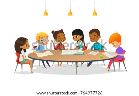 Boys And Girls Sitting Around Round Table, Studying, Reading Books And  Discuss Them.
