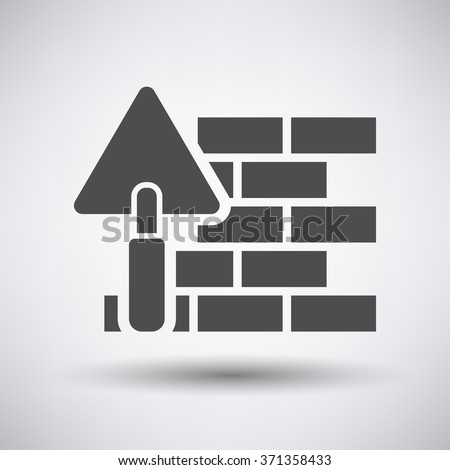 Brick wall with trowel icon on gray background with round shadow. Vector illustration.