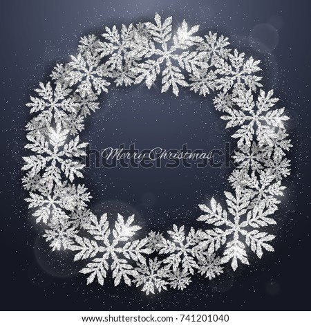 Christmas and new year dark blue background with christmas wreath made of  silver glittering snowflakes. Merry Christmas greeting card