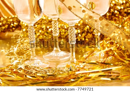 Close-up of fluted champagne glasses i n a golden background	0