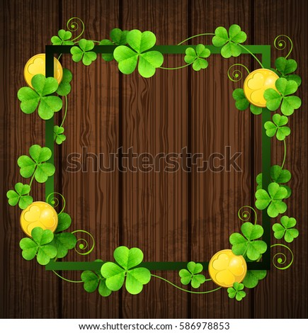 Clover leaves and golden coins in green frame on a wooden background. Design for St. Patrick's day.