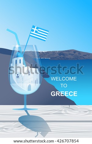 Cocktail glass with white church with blue dome at Santorini island