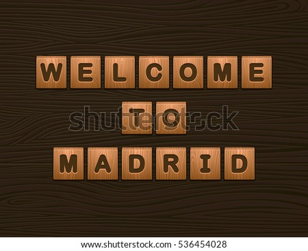 "Cubes with letters ""Welcome To Madrid"" on wooden board for Web"