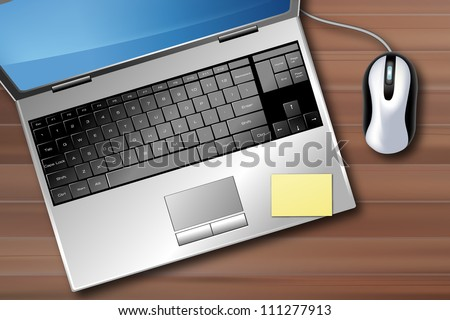 desk with a laptop, mouse, and a post-it stuck on the keyboard