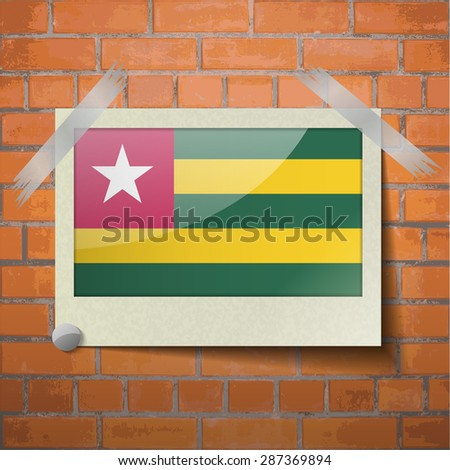 Flags of Togo scotch taped to a red brick wall. Vector - stock vector