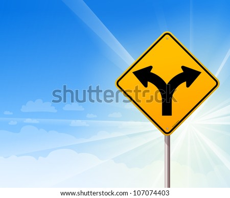 Fork in the road on blue sky - Yellow roadsign of forked road on a blue sunshine background