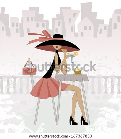 girl in a hat sits in cafe against the old city