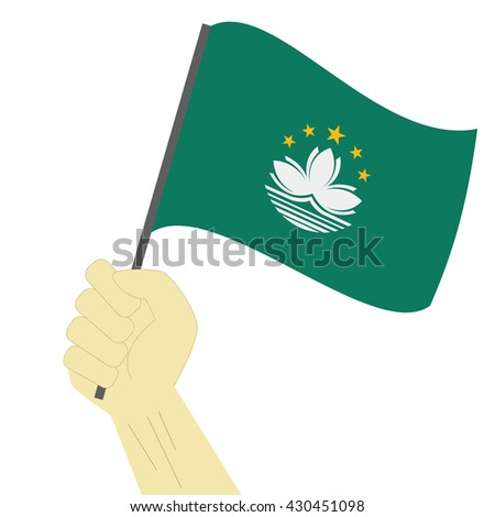 Hand holding and raising the national flag of Macao
