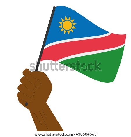 Hand holding and raising the national flag of Namibia