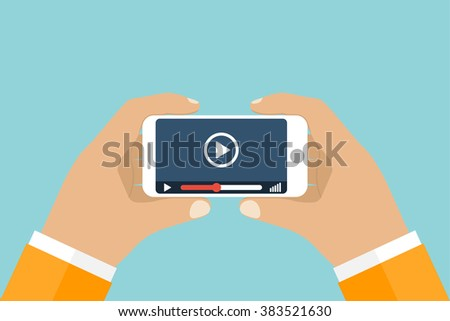 Hand holds smartphone. Video player application on your mobile phone screen. Watching videos on the phone.  Vector flat. Mobile video streaming technologies.