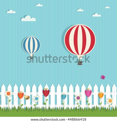 hot air balloons on a landscape background with picket fence, grass and flowers