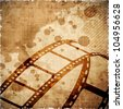 Illustration of a film stripe or film reel on grungy brown movie background. EPS 10 - stock photo