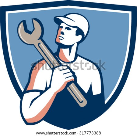 Illustration of a tradesman mechanic wearing hat holding spanner on shoulder looking up to the side set inside shield crest on isolated background done in retro style.  - stock vector