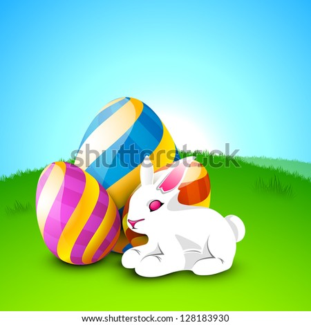Little cute Easter rabbit with painted eggs on nature background.