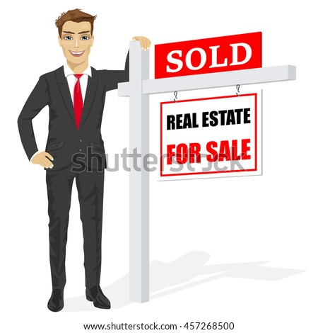 Male real estate agent standing next to a sold for sale sign