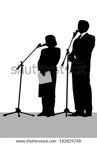 Man and woman in business suits at microphones