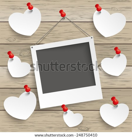 Paper photoframe and hearts with tacks on the wooden background. Eps 10 vector file. - stock vector