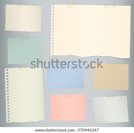 Pieces of torn colorful lined note paper on gray background